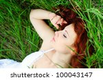 Resting girl portrait, lying in grass field. Outdoor. - stock photo