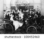 Newlyweds leaving wedding in carriage - stock photo