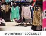 Variety of sweaters and other clothes in mall - stock photo