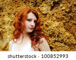 Young redhead sensual woman portrait standing near the rock. Outdoor. - stock photo