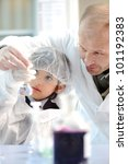 Teacher and young student in chemistry lab - stock photo