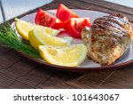 Close-up of fried chicken served with lemon and tomatoes - stock photo