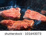 BBQ with fiery steak on the grill - stock photo
