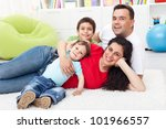 Happy young family together with two kids laying on the floor - stock photo
