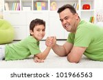 Happy father and son playing arm wrestling, lying on the floor - stock photo