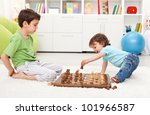 Small kids playing chess in their room - stock photo