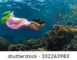 Fashion in tropical paradise. Beautiful model underwater watching colorful coral reef full of yellow fish - stock photo