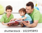 Kids reading story book with their father - sitting on the floor - stock photo