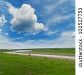 river in green grass under cloudy sky - stock photo