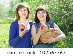 Happy young women with apple harvest in orchard - stock photo