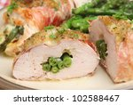 Baked chicken breast stuffed with green bean and cheese and wrapped in Parma ham - stock photo
