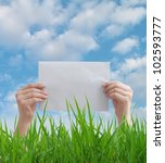 hands holding the paper against the background of grass and sky - stock photo