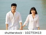Young Asian couple in love on the beach. - stock photo