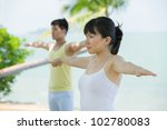Asian couple doing yoga on the beach. - stock photo