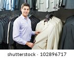 Young man choosing suit jacket during apparel shopping at clothing store - stock photo