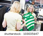 Young woman choosing raincoat outerwear during clothing shopping at apparel store - stock photo