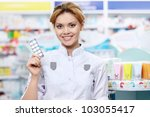 The pharmacist at the pharmacy with tablets - stock photo