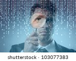 Young businessman observing a binary code on a screen through a magnifying glass - stock photo