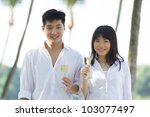 Happy young couple enjoying champagne on a tropical beach. - stock photo