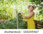 Female gardener composting grass in garden - stock photo