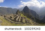 Machu Picchu, main gate, surrounding wall and exterior stairway under uneven sunlight. - stock photo