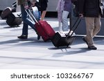 traveling people with their trolleys at a train platform - stock photo