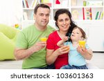 Family with child having fresh fruit juice at home - stock photo