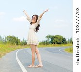 Young asian woman stan on the road in a happy feel. - stock photo