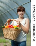Happy young woman with vegetables harvest in hothouse - stock photo
