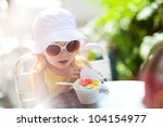Outdoor portrait of adorable little girl eating ice cream - stock photo