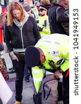 London, United Kingdom, 07th March 2018:-  Police search an unknown protester during the Stop The War Coalition's protest against the visit to the UK by the Crown Prince of Saudi Arabia - stock photo