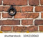 Old european brick wall with metal ring - stock photo