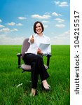 smiley businesswoman with documents showing thumbs up at the field - stock photo