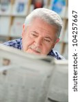 Senior man with mustache reading newspaper in library - stock photo