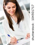 Business woman signing a contract  and smiling - stock photo