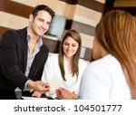 Couple on a business trip doing check-in at the hotel - stock photo