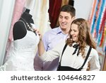 Young man and woman choosing wedding dress during apparel shopping at clothing store - stock photo