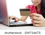 Smiling woman with laptop and a credit card isolated on white - stock photo