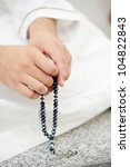 Using rosary, beads in hands - stock photo