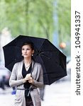 Pretty and young woman with umbrella - stock photo