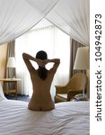 Naked young woman in bed with sensitive mood - stock photo