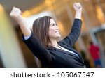 Successful business woman with arms up celebrating - stock photo