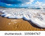 Waves wash over golden sand on Australian beach - stock photo