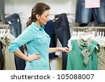 Young woman choosing garments during clothing shopping at apparel store - stock photo