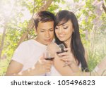 young couple drinking wine under the lilac bush - stock photo