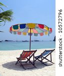 Beach umbrella and two chairs on a sandy beach of Phi-Phi island, Thailand - stock photo