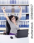 Happy Asian Business woman expressing her success by stretching her hands, shot at office - stock photo