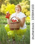 Happy mature woman with vegetables in garden - stock photo