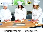Beautiful female chefs kneading dough. Watching and learning - stock photo