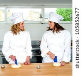 Two pretty female chefs looking at each other while kneading dough - stock photo